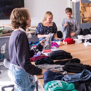 Tonåringar viker och sorterar kläder