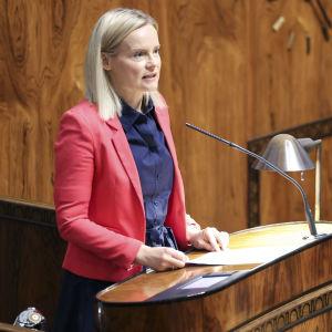 Riikka Purra står vid ett talarpodium i riksdagen.