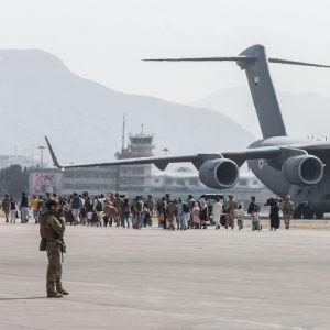 Flygfältet i Kabul. En folksamling framför en Air Force Boeing C-17. Soldater övervakar.