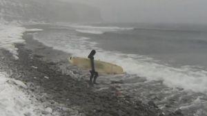 Surfare går ner i det kalla vattnet.