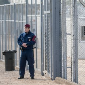 Containrar som används för logi i en ungersk transitzon på gränsen mellan Ungern och Serbien. Området är omgärdat av ett stängsel och taggtråd, en vakt står utanför området. Fotot från ett läger nära den ungerska staden Tompa, den 6 april 2017.