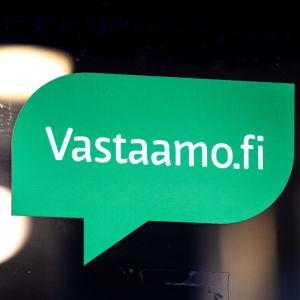 Logotyp i form av en grön pratbubbla och med texten vastaamo.fi på en glasdörr.