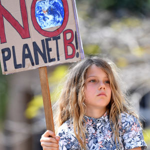 "Liten flicka på en mans axlar håller i en skylt med texten ""There is NO planet B""."