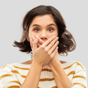 Kvinna håller båda händerna framför munnen och ser förvånad ut.