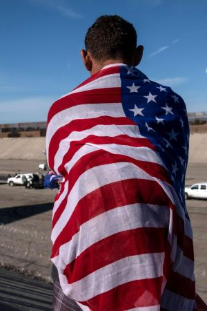 En migrant från Centralamerika insvept i USA:s flagga blickar ut över den torra flodbädden nära gränsövergången El Chaparral, Tijuana vid gränsen mellan USA och Mexiko