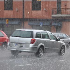 Bil som kör i regn. Det kommer en störtskur.