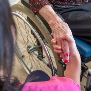En vårdare håller i en äldre persons hand. Den äldre sitter i rullstol.