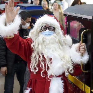 Julgubben vinkar och står vid ett lok.