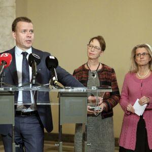 Petteri Orpo står och håller tal. I bakgrunden syns Kai Mykkänen, Sari Essayah, Päivi Räsänen och Harry Harkimo.