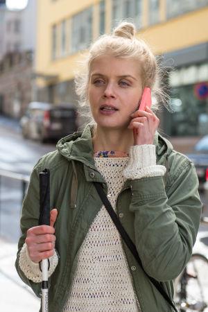 Donna (Alina Tomnikov) kuuntelee kadulla puhelintaan toisessa kädessä hänellä on valkoinen keppi.