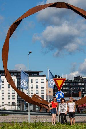 Tre personer poserar framför en cirkelformad skulptur gjord av rostigt stål.