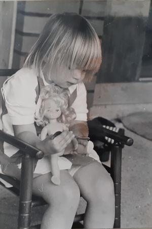 Mela, Mikaela Nyholm som barn med en docka i sin famn, sittande i en liten gungstol. Svartvit bild.