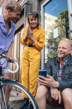 AIKUISET-sarjan Oona, Arttu ja Markku hymyilevät yhdessä kadulla. Artun pyörä näkyy etualalla, Markku pitelee puhelinta.