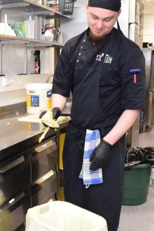 En person i ett restaurangkök slänger mat i sopkärl för bioavfall.
