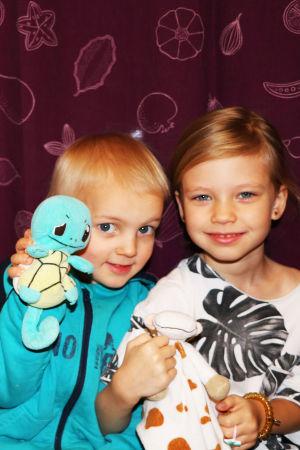 Tre barn, två pojkar till vänster och en flicka till höger, sitter på en bänk framför en lila gardin och håller varsitt kramdjur i handen.