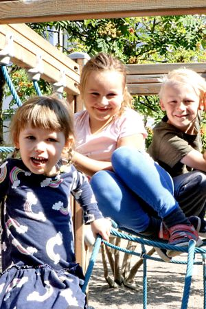 Fem dagisbarn i sommarkläder klänger i en klätterställning.