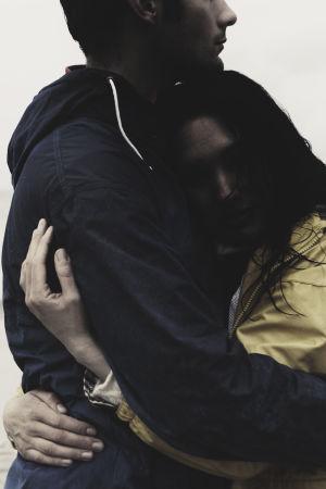 Kvinna i gul jacka kramar en längre man på en strand i dimmigt väder.