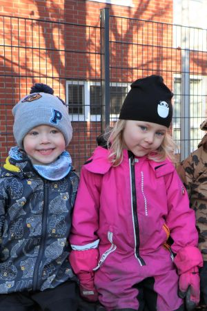 Tre varmt klädda dagisbarn vid rutschkana.