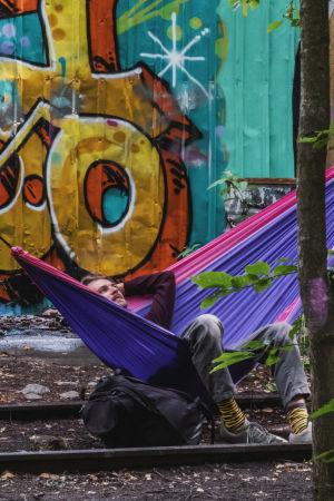 Man ligger i färggrann hängmatta fäst mellan ett par träd som sticker upp mellan järnvägsspår. I bakgrunden färggann graffittivägg.
