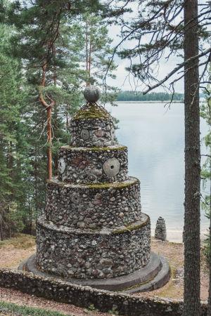 Minnesmärke av sten intill sjö.