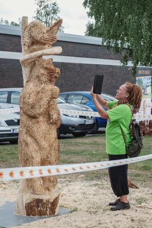 Rastapäinen nainen ottaa valokuvaa karhun mallisesta puuveistoksesta