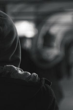 Person med huva på huvudet som står med ryggen vänd mot kameran och stirrar in i en tunnel.