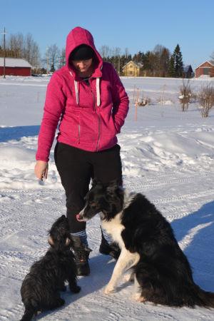 maria kalenius på sin gård med två svarta hundar en snöig dag