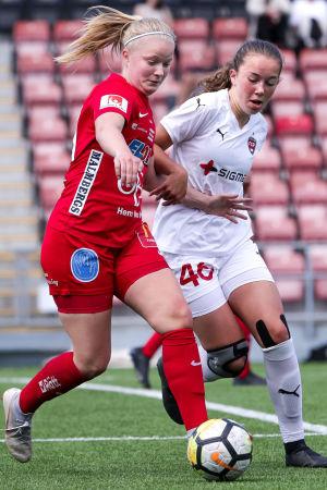 Rebecka Mannström iklädd röd spelardräkt kämpar om bollen under en fotbollsmatch.