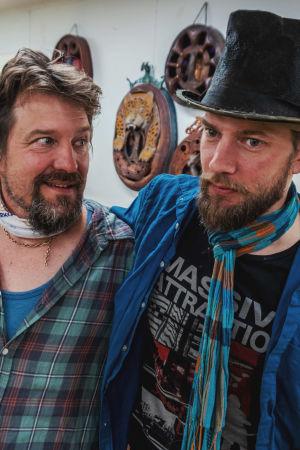 Kaksi miestä seisovat puutaiteilijan työskentelytilassa ja pitävät toisiaan hartioista. Vasemmanpuoleisella miehellä on parta ja ruudullinen flanelllipaita. Oikeanpuolinen, myös parrakas mies, on pukeutunut silinterihattuun ja ruudulliseen kaulahuiviin.