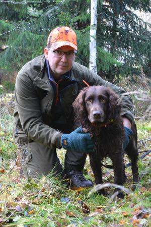 Magnus Nylander iklädd gröna jaktkläder sitter på huk tillsammans med Choko.