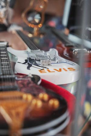 Vitrinhylla med miniatyrgitarrer, på en av dem står det Elvis.
