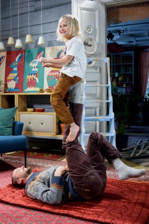 En man ligger på golvet med ett ben i luften som en pojke sitter på.