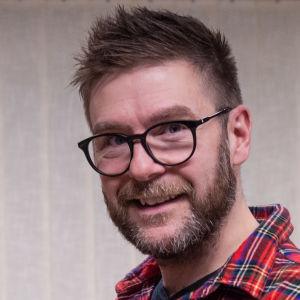En man med skägg och glasögon, samt iklädd en rödrutig skjorta, ler mot kameran.