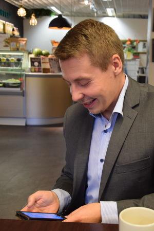Barnombudsman Tuomas Kurttila på kafé med mobiltelefon i hand