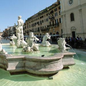 Suihkulähde, jossa useita vettäsylkeviä patsaita, Piazza Navonalla Roomassa. Talot ympäröivät aukiota.