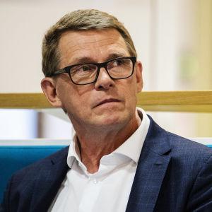Matti Vanhanen sitter på en soffa. Han tittar lite uppåt och åt sidan.