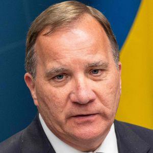 Stefan Löfven, en vit man, i kostym med Sveriges flagga i bakgrunden.