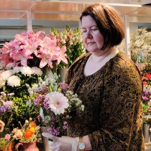 En kvinna står i en blomaffär och håller i en blombukett. Hon ser på den fundersamt.