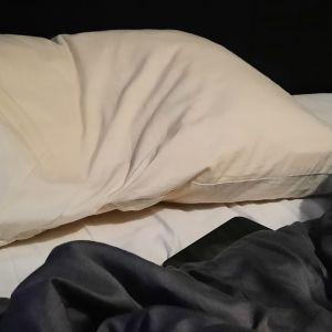 En dyna och ett täcke i en tom säng