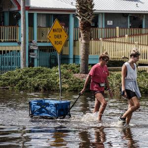 Två kvinnor plumsar genom vattnet på en översvämmad gata i Alabama efter att stormen Sally dragit fram i september.