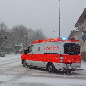 En ambulans på utryckning svänger runt ett gathörn på snöiga gator.