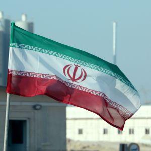 Irans flagga vajar framför iranskt kärnkraftverk.