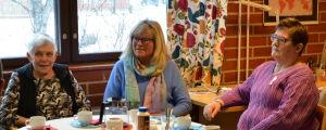Gunhild Lindström, Hannele Alho och Rose Nyström sitter kring ett kaffebord.