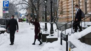 Tre personer går från Borgå stadshus till en väntande svart bil. I mitten går Sanna Marin som lyfter handen i en hälsning.