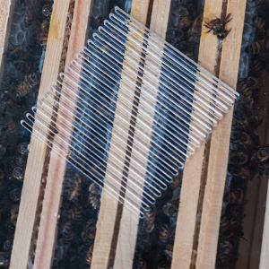 Rader av träramar, mellan dem skymtar bin. Överst ett plastlock med lufthål.