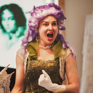 En sångerska klädd i peruk sjunger opera.
