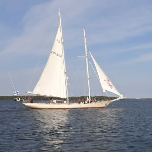 Skolfartyget Helena med vita segel möter en liten segelbåt.