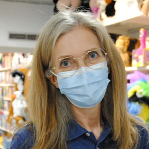 En kvinna med ljust hår, tunna glasögon och ansiktsmask står inne i en leksaksaffär.