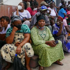 Tiotals människor sitter och väntar utanför en byggnad