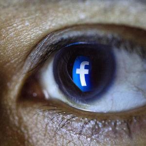 Ett öga med en spegling av Facebooks logo i irisen.